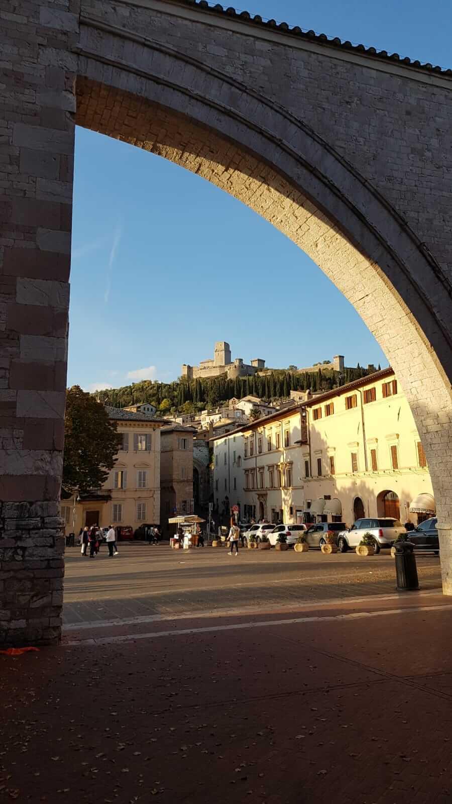 Assisi : vista di una piazza da un arco